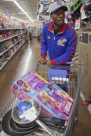 KU sophomore Naadir Tharpe looks for the last gifts on Thursday, Dec. 13, 2012, during the Jayhawks' holiday shopping excursion to Wal-Mart.