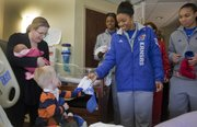 Stacia Griffith, Lawrence, left, holds her 1-day-old daughter Maggie, while her son, Charlie, receives a gift from Kansas University women's basketball player CeCe Harper. Members of the KU women's basketball team visited patients Monday at Lawrence Memorial Hospital and passed out Jayhawk gifts. Other players in the photo are Chelsea Gardner, background left, and Markisha Hawkins, right.