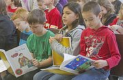 Drew Foster, 8, from left, Layla Harjo, 9, and Spencer Meyer 8, look over their new books Tuesday during an assembly at Prairie Park School. Hundreds of students created their own books, then received a free hardback copy from Studentreasures Publishing in Topeka. The purpose of the program is to encourage creativity while reinforcing basic written communication skills.