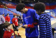 Donovan Young, right, watches as his older brother, KU forward Kevin Young signs an autograph for Trentyn Harris of Frontenac, Kan., after Tuesday's game against Richmond at Allen Fieldhouse.