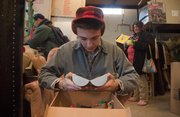 Ian Schneck, 18, of Lawrence, sorts through a box of toys Wednesday at the Social Service League Thrift Store. All items in the store are donations from community members.