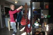 Debra Rukes, owner of Kretyen, 2116 W. 25th street, hangs some Guatemalan purses in her quaint store full of fair trade items.