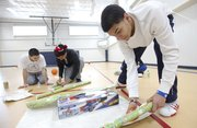 Lawrence High sophomore Anthony Bonner snips away at some wrapping paper as he and his teammates — sophomore Sam Stephens, left, junior Anthony Riley and junior Isaiah Boldridge, partially obscured — ready gifts for a family they adopted through Lawrence Family Promise on Thursday, Dec. 20, 2012, at Immanuel Lutheran Church, 2104 Bob Billings Parkway.