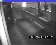 Surveillance video photo from a  Dec. 13 robbery at Cheers Liquor, 1414 West 6th Street. The photo, from the Dunkin' Donuts drive-thru window, shows the suspect crossing Sixth Street before he covered his face and approached the liquor store to the west.