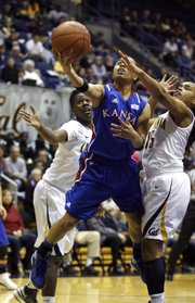 Kansas' Angel Goodrich, center, drives between California's Afure Jemerigbe, left, and Brittany Boyd in the first half. KU fell to Cal, 88-79, on Friday, Dec. 21, 2012, in Berkeley, Calif.
