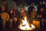 "A crowd gathers around a fire and forms a drum circle as they each say what personal baggage that they are giving up while offering cedar leaves to the fire Friday outside of the Percolator gallery in downtown Lawrence. The Percolator was hosting a new exhibit, called ""The Baggage Show,"" that coincided with the winter solstice and the end of the Mayan calendar."