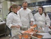 From left, Bailey Campbell, a Eudora sophomore in her first year in culinary arts at the Eudora-De Soto Technical Education Center at Eudora High School, her instructor Rick Martin and sophomore Madison McGinness prepare sweet potato gratin Saturday at Eudora High School. Students in the culinary arts program, along with help from friends and parents, were preparing six gourmet meals for families in need as part of an Adopt-A-Family program.