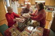 Winona Marks, left, and Mark and Shanon Marks pack up dozens of cookies on Christmas Eve. For at least 15 years, the family has made and delivered cookie trays to residents in the Lawrence community who work the night shift in various emergency roles, such as firefighters, nurses and police officers.