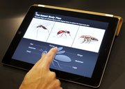 An Apple employee demonstrates an interactive feature of iBooks 2 for iPad, Thursday, Jan. 19, 2012 in New York. Starting with the new semester in January, Lawrence public schools will begin pilot testing a new web-based tool that, among other things, will allow teachers to dispense with traditional hardbound textbooks and replace them with &quot;open-source&quot; learning material.
