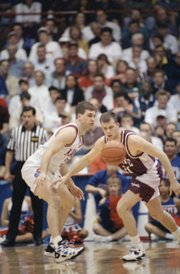 In this file photo from March 16, 1995, Kansas' Greg Gurley, left, and Colgate's Tucker Neale go after a loose ball during a first-round NCAA Tournament game in Dayton, Ohio.