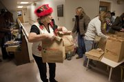 Volunteer Jacque Knighton prepares to help distribute about 600 free Christmas meals to those who could not attend the Free Community Christmas Day Dinner Tuesday at First United Methodist Church, 946 Vermont St.