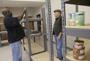 Ulysses Demby, a Just Food employee who manages food drives for the agency, left, and Just Food volunteer Fairley McCain, put together new shelving for the food bank at the Just Food pantry, 1000 E. 11th Street. The Ballard Center, Just Food, Penn House and Salvation Army are joining forces to create a food bank cooperative.