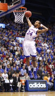 With a hand behind his head, Kansas guard Travis Releford comes in for a dunk against American during the first half on Saturday, Dec. 29, 2012 at Allen Fieldhouse.