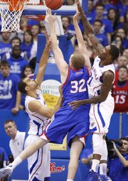 Kansas defenders Perry Ellis, left, and Jamari Traylor collapse on American forward Stephen Lumpkins during the first half on Saturday, Dec. 29, 2012 at Allen Fieldhouse.