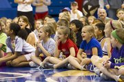 Campers listen and laugh while members of the Kansas women's basketball team introduce themselves as the team hosted its annual Holiday Hoops Clinic, Sunday afternoon at Allen Fieldhouse. Nearly 300 children, in kindergarten through eighth grade, worked through various drills, including defense, ball handling, free throws and rebounding, with the women's basketball team and coaches.