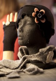 A head warmer, fingerless glove and scarf by Jerry Dowdle of Lawrence. Dowdle upcycles sweaters and other clothing items by deconstructing them and creating new clothes and accessories. 