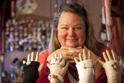 Jerry Dowdle of Lawrence is pictured with fingerless gloves and accessories she has upcycled from used or damaged sweaters. Dowdle calls her business TerranJerran: Taming the Tattered and sells on Etsy and at arts and crafts fairs.