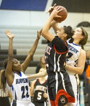 Lawrence High junior Kionna Coleman has her shot blocked by Michaela Crall while vashti Neal (22) defends during Lawrence High's game against Olathe Northwest, Friday, Jan. 4, 2013 in Olathe.
