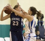 Topeka Heritage's Lyndsey Cowin (23) holds the ball away from Kristen Finger during Veritas' game against Topeka Heritage, Saturday, Jan. 5, 2012 in Eudora.