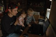 "Brian Bolen, 32, of Shawnee, works on his laptop with the ""help"" of his children, Coleen, 1, and Daniel, 2. After two layoffs, Bolen is working on earning a degree online through Johnson County Community College."