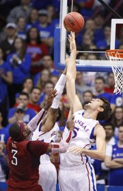 Kansas center Jeff Withey reaches high to tip away a shot by Temple forward Anthony Lee during the first half on Sunday, Jan. 6, 2013 at Allen Fieldhouse. Also pictured is Kansas guard Ben McLemore.