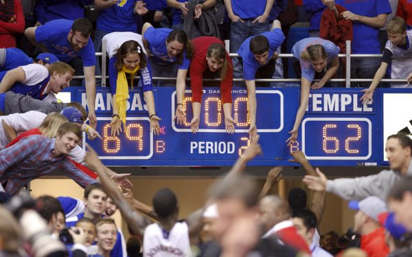 Kansas fans reach below the scoreboard to slap hands with the Jayhawks after their 69-62 win over Temple on Sunday, Jan. 6, 2013 at Allen Fieldhouse.