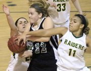 Free State's Scout Wiebe (22) drives between Shawnee Mission South's Shiya Pouncil, left, and Siera Roberts (11) in a 49-46 FSHS loss on Monday, Jan. 7, 2013, at SM South.