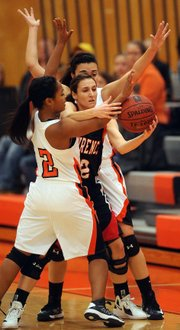 Lawrence High's Emma Kelly, center, is pressured by Shawnee Mission Northwest defenders on Tuesday, Jan. 8, 2012, in Shawnee.