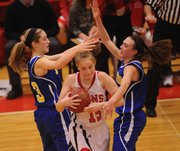 Lawrence High senior Kylie Seaman (15) tries to escape Olathe South defenders Courtney Jones (3) and Lindsey Delana (15) on Friday, Jan. 11, 2013, at LHS.