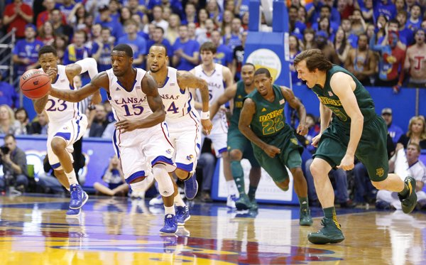 Kansas guard Elijah Johnson takes off up the court past Baylor guard Brady Heslip after a steal during the first half on Monday, Jan. 14, 2013 at Allen Fieldhouse.