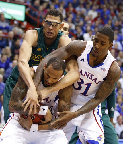 Kansas guard Travis Releford comes away with the ball as both Baylor center Isaiah Austin and teammate Jamari Traylor lock their arms around him during the second half on Monday, Jan. 14, 2013 at Allen Fieldhouse.