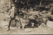 William Ederwein of Goff, Kan., sits on a keg near a spring where bottled beer was placed to cool during the summer months at the turn of the century. Prohibition shut down most Kansas breweries, but many residents continued, though cautiously, to obtain and enjoy beer.