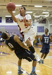 Lawrence High freshman Justin Roberts (5) is called for an offensive foul as he plows through Jordan Hester (0) during Lawrence High's opening round game against Wichita East in the Topeka Invitational Tournament, Thursday, Jan. 17, 2013 at Topeka West High School. The Lions held on for a 63-57 victory and will play tomorrow at 6:45 p.m.