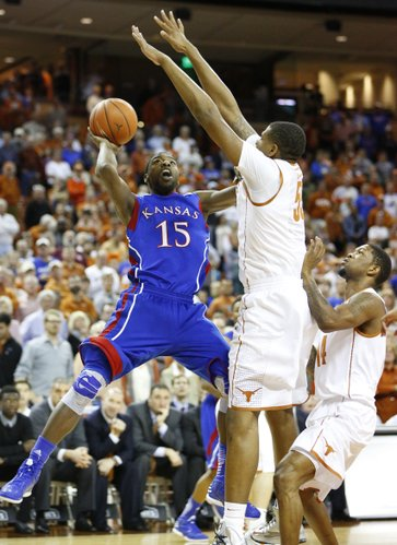 Kansas guard Elijah Johnson is defended by Texas players Cameron Ridley, left, and Julien Lewis during the first half on Saturday, Jan. 19, 2013 at Frank Erwin Center in Austin, Texas.