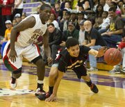Lawrence High sophomore Anthony Bonner, right, loses control of the ball as he stumbles trying to drive past Oshai Clark (35) during Lawrence High's game against Highland Park in the championship game of the Topeka Invitational Tournament, Saturday, Jan. 19, 2013 at Topeka West High School. The Lions fell 69-47 and ended up with second place honors.