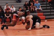 Shawnee Mission Northwest junior LaPhonso McKinnis, shown here wrestling Royal Valley senior Tristen Matthews at the Dec. 8 Cougar Invitational, has won two tournaments and placed third at two others this season. Less than one year ago, McKinnis turned himself in for theft, beginning a turnaround that finds him ranked third in his weight class as of Jan. 22.