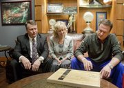 Kansas basketball coach Bill Self signs a piece of the floor from the New Orleans Superdome court used during the 2012 NCAA championship game between KU and Kentucky. Joe and Nancy Jones of Lawrence, left, acquired 50 pieces of the Final Four floor, some of which were then signed by Self on Jan. 23 and will be auctioned off for charity.