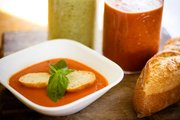 Creamy Tomato soup garnished with slices of baguette and some basil is one of the endless kinds of soups that can be exchanged at parties on National Soup Swap Day on Saturday.