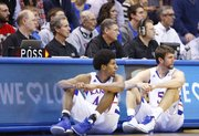 Scoreboard operator Robbie Vannaman, far left, keeps watch of the game as Kansas players Kevin Young and Jeff Withey look to check in during the first half of the Jayhawks' game against American University on Saturday, Dec. 29, 2012, at Allen Fieldhouse.