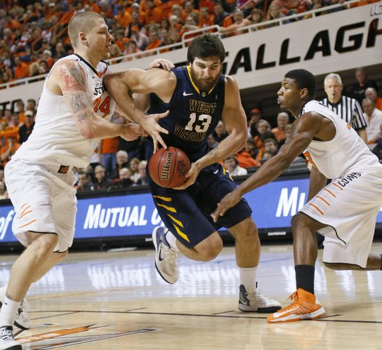 West Virginia's Deniz Kilicli (13) drives between Oklahoma State's Philip Jurick, left, and Marcus Smart during Saturday's game in Stillwater, Okla.