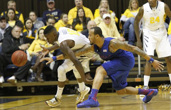 Kansas guard Travis Releford (24) attempts a steal from West Virginia&#39;s Eron Harris (10) in the Jayhawks&#39; game against the Mountaineers on Monday night in Morgantown, W.Va.