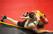 Lawrence High's Garrett Girard holds Blue Valley Southwest's Ben Harmon to keep Harmon from escaping out of bounds during their wrestling match in the 126-pound weight class, Wednesday, Jan. 30, 2013, at LHS.