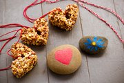 Instead of candy, kids can make eco-friendly valentines: clockwise from left, birdseed cakes, friendship bracelets and painted rocks.