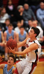 LHS senior Jake Mosiman (3) makes a easy layup against Shawnee Mission East on Friday, Feb. 1, 2013.