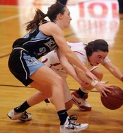 LHS senior Anna Wright (24) goes for a steal on Shawnee Mission East's (23) Erin McGinley on Friday, Feb.1, 2013, at LHS.