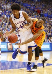 Kansas forward Kevin Young and Oklahoma State guard Markel Brown compete for a loose ball during the first half on Saturday, Feb. 2, 2013 at Allen Fieldhouse.