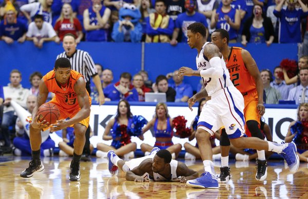 Kansas guard Elijah Johnson watches from the floor as Oklahoma State guard Marcus Smart recovers a fumbled ball by Johnson with seconds remaining in the game on Saturday, Feb. 2, 2013 at Allen Fieldhouse. The turnover nullified the the Jayhawks' comeback effort. At right is Kansas guard Ben McLemore and Oklahoma State guard Markel Brown.