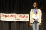 "Bishop Seabury Academy eighth-grader Abena Peasah flashes a smile at the judges after winning the Douglas County Spelling Bee on Saturday at Southwest Middle School. Abena won the spelling bee by correctly spelling the world ""stabilizer."""