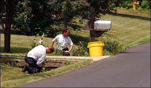 In 2002, Lawrence Police Academy Director Trent McKinley, left, and police recruit Mark Unruh check for evidence along Learnard Avenue in the slayings of Pete Wallace and Wyona Chandlee. Investigators continued pursuing leads of nearby burglaries that might be related to the slayings. Lawrence Journal-World file photo.
