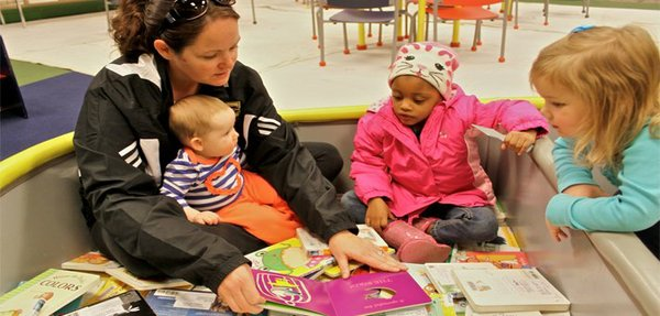 "Melissa Ranson reads to children at the Topeka-Shawnee County Public Library. Experts say youngsters benefit from early exposure to books and reading. ""She enjoys it,"" Ranson said of her three-year-old daughter, Landry, right."